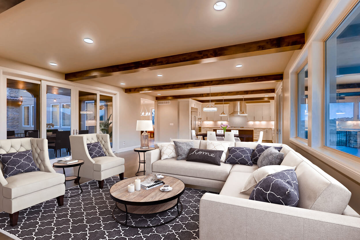 Large furnished great room with navy blue accent pillows and carpet