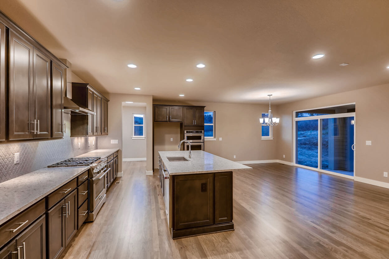 Great Room Kitchen With Big Island and Brown Cabinets